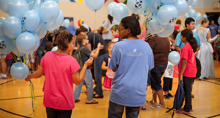 The volunteer team passes out balloons with the backpacks